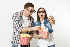 Young shocked couple, woman and man in 3d glasses watching movie film on date holding bucket of popcorn, plastic cup of. Young shocked couple, women and men in royalty free stock images