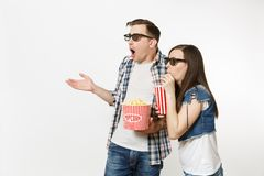 Young shocked couple, woman and man in 3d glasses watching movie film on date, holding bucket of popcorn and plastic cup. Young shocked couple, women and men in royalty free stock photography
