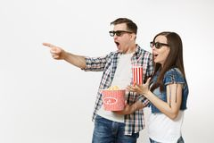 Young shocked couple, woman and man in 3d glasses watching movie film on date, holding bucket of popcorn and plastic cup. Young shocked couple, women and men in stock photography