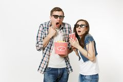 Young shocked couple, woman and man in 3d glasses watching movie film on date, holding bucket of popcorn and plastic cup. Young shocked couple, women and men in stock images