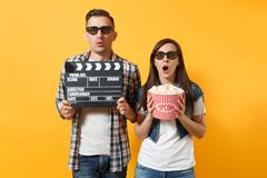 Young shocked couple woman man in 3d glasses watching movie film on date holding classic black film making clapperboard royalty free stock image