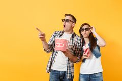 Young shocked couple woman man in 3d glasses watching movie film on date holding bucket of popcorn plastic cup of soda. Young shocked couple women men in 3d royalty free stock photo