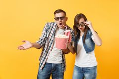 Young shocked couple woman man in 3d glasses watching movie film on date holding bucket of popcorn plastic cup of soda. Young shocked couple women men in 3d royalty free stock image