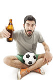 Young shocked emotional supporter sitting on the floor and watching soccer with beer Royalty Free Stock Photos