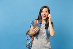 Young shocked excited woman student with opened mouth with backpack, earphones listening music holding mobile phone royalty free stock images