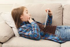 Young shocked girl with digital tablet at home. Surprised little girl using digital tablet, lying on beige couch at home, copy space. Shocking news, lottery Stock Image