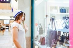 Young shocked girl looking at shop window with shoes and bags in Shopping Mall. Shopper. Sales. Shopping Center. Space for text. S Stock Images
