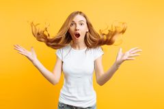 Young shocked girl shocked by good news, screaming with happiness over yellow background stock images