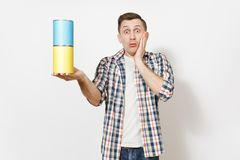 Young shocked handsome man holding empty paint tin cans with copy space and keeping hands near face isolated on white. Background. Instruments for renovation stock images