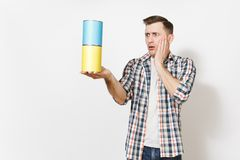 Young shocked handsome man holding empty paint tin cans with copy space and keeping hands near face isolated on white. Background. Instruments for renovation royalty free stock photos