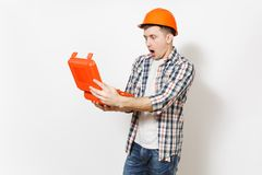 Young shocked handsome man in protective orange hardhat holding opened case with instruments or toolbox isolated on. White background. Instruments for stock images