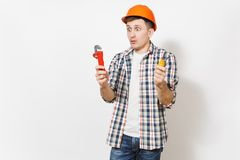 Young shocked handsome man in protective orange hardhat holding toy screwdriver and adjustable wrench isolated on white stock images