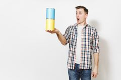 Young shocked man in casual clothes holding empty paint tin cans with copy space isolated on white background. Instruments, accessories, tools for renovation stock images