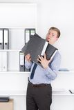 Young shocked man is holding several files in the office Royalty Free Stock Image