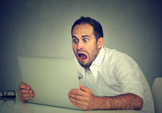 Young shocked man with laptop computer sitting at table royalty free stock photo