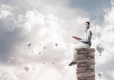 Man student on stack reading book and aerostats flying around stock photo