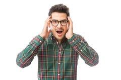 Shocked Man Touching Face Over White Background. Young shocked man touching face while standing over white background stock photo