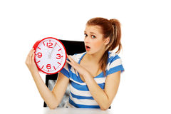Young shocked teenage woman looking at clock Stock Photography