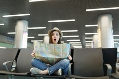 Young shocked traveler tourist woman with crossed legs hold paper map, search route waiting in lobby hall at. International airport. Passenger traveling abroad stock photo