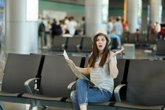 Young shocked traveler tourist woman holding paper map, search route, spreading hands wait in lobby hall at airport. Passenger traveling abroad on weekends stock photo