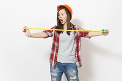 Young shocked woman in casual clothes, protective construction helmet holding toy measure tape isolated on white. Background. Instruments, tools for renovation royalty free stock images