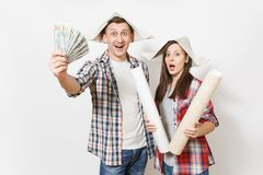 Young shocked woman, man in casual clothes holding bundle of dollars, cash money and wallpaper roll. Couple isolated on royalty free stock photos