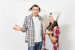 Young shocked woman, man in casual clothes and newspaper hats spreading hands. Couple isolated on white background stock images