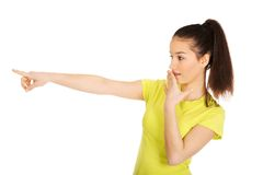 Young shocked woman pointing aside. Royalty Free Stock Photo