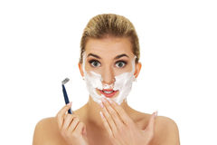 Young shocked woman shaving her face with a razor Stock Photography