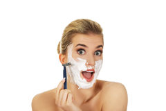 Young shocked woman shaving her face with a razor Royalty Free Stock Photo
