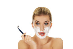 Young shocked woman shaving her face with a razor Stock Images