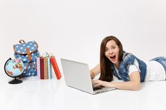 Young shocked woman student in denim clothes working on laptop pc computer lying near globe, backpack, school books. Isolated on white background. Education in stock photography