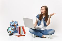 Young shocked woman student holding using laptop pc computer spreading hand sitting near globe backpack, school books. Isolated on white background. Education royalty free stock image