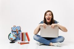 Young shocked woman student with opened mouth holding clinging to laptop pc computer sitting near globe backpack school. Books isolated on white background royalty free stock photo