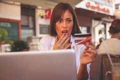 Young girl using credit card. Girl was bankrupt. Young shocking girl using credit card in cafe. Girl was bankrupt stock photo