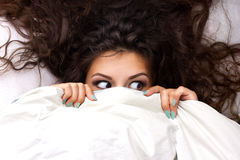 Young shocking  woman. With beautiful brown  dishevelled curls hair in the bed Royalty Free Stock Photo