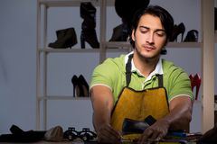 The young shoemaker in workshop at night. Young shoemaker in workshop at night stock photo