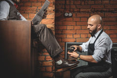 Young shoeshiner polishing footwear in front of the client Royalty Free Stock Photography