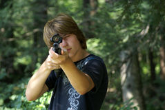Young Shooter. Fifteen years old boy hoding a gun in the forest Stock Photography