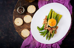 Young shoots of asparagus with ham and chicken egg yolk on toast Stock Images