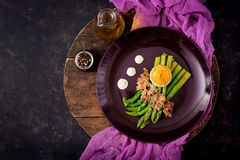 Young shoots of asparagus with ham and chicken egg yolk Stock Photos