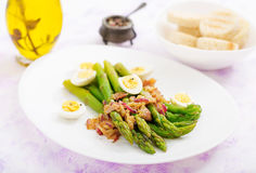 Young shoots of asparagus with ham and quail eggs. On plate Stock Photo