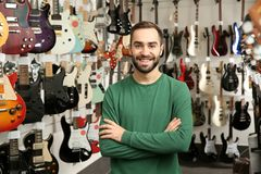 Shop assistant near guitars in music store stock photo