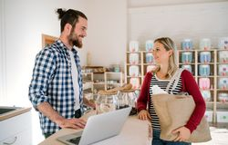 Young shop assistant serving an attractive woman in a zero waste shop. royalty free stock photos