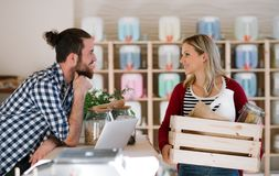 Young shop assistant serving an attractive woman in a zero waste shop. Young male shop assistant with laptop serving an attractive women in a zero waste shop royalty free stock images
