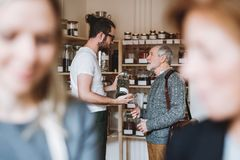Young shop assistant serving a senior man in a zero waste shop. stock images