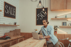 Young shop owner using laptop while working indoors. Concentrated young shop owner using laptop while working indoors Stock Photography
