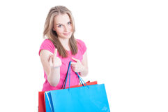 Young shopaholic doing a rude gesture while doing shopping Royalty Free Stock Images