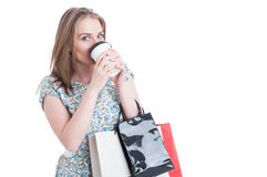 Young shopaholic drinking hot coffee and doing shopping Stock Photography