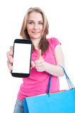 Young shopaholic holding phone with empty screen and showing thu Royalty Free Stock Photo